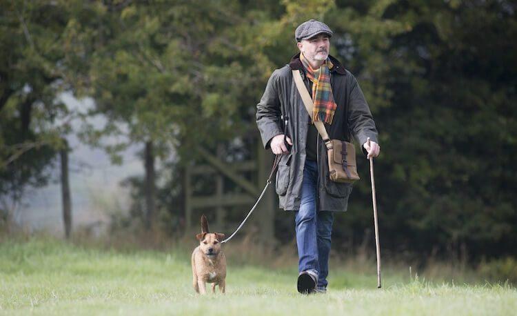 Man Walking A Patterdale Terrier